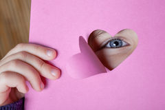 Niño que mira a través de una tarjeta de la dimensión de una variable del corazón Fotografía de archivo libre de regalías