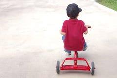 Niño que monta un triciclo Foto de archivo