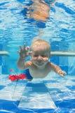 Niño que nada bajo el agua para una flor roja en la piscina Fotos de archivo