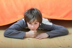 Niño que oculta debajo de cama Foto de archivo libre de regalías
