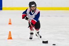 Niño que patina con un duende malicioso en la práctica del hockey sobre hielo Imagen de archivo libre de regalías