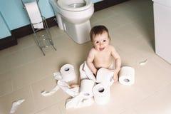 Niño que rasga para arriba el papel higiénico en cuarto de baño Fotos de archivo