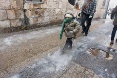 Niño que recorre en las nevadas de Jerusalén Imagen de archivo libre de regalías