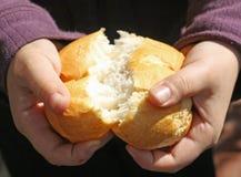 Niño que rompe un pedazo de pan con las manos Imagenes de archivo