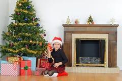 Niño que sacude el regalo de Navidad por el árbol Imagen de archivo