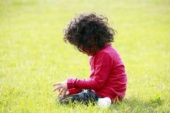 Niño que se sienta en la hierba Foto de archivo libre de regalías