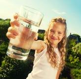 Niño que se sostiene de cristal con agua Imagen de archivo