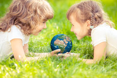 Niño que sostiene el planeta de la tierra en manos Imagen de archivo libre de regalías
