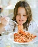 Niño que tiene espagueti Imagenes de archivo