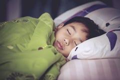 Niño sano Pequeño muchacho asiático que duerme pacífico en cama Imagen de archivo libre de regalías