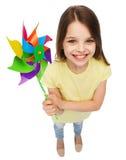 Niño sonriente con el juguete colorido del molino de viento Foto de archivo