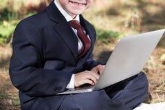 Niño sonriente en traje de negocios delante de un ordenador portátil que trabaja en Internet Imagen de archivo