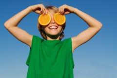 Niño sonriente que juega con la fruta Imágenes de archivo libres de regalías