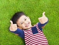 Niño sonriente que miente y pulgar para arriba en un prado Imagen de archivo libre de regalías