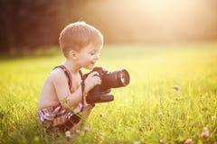 Niño sonriente que sostiene una cámara de DSLR en parque Fotografía de archivo