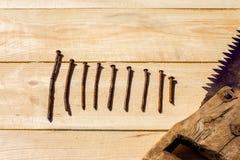 Nio spikar och den rostiga sågen på trägrova plankor Royaltyfria Bilder