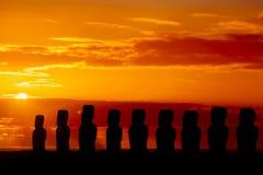 Nio stående moais på den röda och guld- solnedgången Royaltyfria Bilder