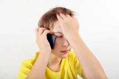 Niño triste con el teléfono móvil Foto de archivo libre de regalías