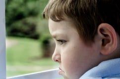 Niño triste que mira hacia fuera la ventana Imágenes de archivo libres de regalías