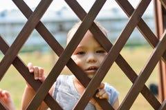 Niño triste y solo que mira hacia fuera a través de la cerca Los problemas sociales, abuso de la familia, niños subrayan emocione Imagenes de archivo