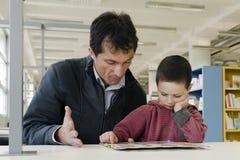 Niño y adulto en biblioteca Fotografía de archivo libre de regalías