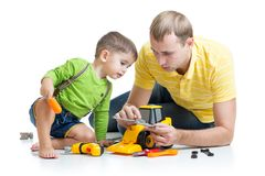 Niño y su tractor del juguete de la reparación del papá Imagen de archivo libre de regalías