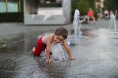 Niño y una fuente de agua que salpica Fotos de archivo