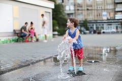 Niño y una fuente de agua que salpica Fotografía de archivo