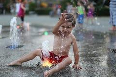 Niño y una fuente de agua que salpica Imagenes de archivo