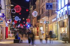 Pedestrian street illuminated by numerous Christmas decoration and shops on each side. Niort, France - December 05, 2017: pedestrian street illuminated by Royalty Free Stock Image