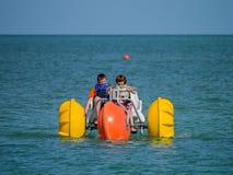 Niños con el barco de paleta en el océano Fotografía de archivo