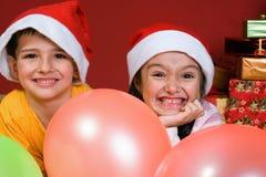 Niños con impulsos por el árbol de navidad Imágenes de archivo libres de regalías