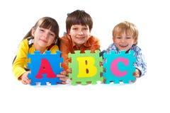 Niños con rompecabezas del alfabeto Imagen de archivo libre de regalías
