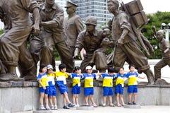 Niños coreanos en el monumento de la guerra Foto de archivo