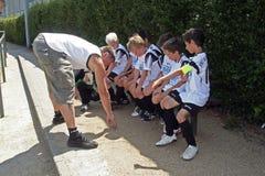 Niños de enseñanza del amaestrador fútbol Fotos de archivo libres de regalías