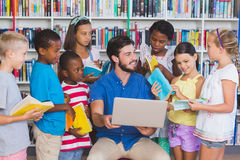 Niños de enseñanza del profesor en el ordenador portátil en biblioteca Fotografía de archivo