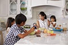 Niños de organización de la madre ocupada en el desayuno en cocina Imagen de archivo libre de regalías