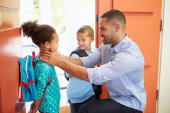 Niños de Saying Goodbye To del padre como se van para la escuela Imagenes de archivo