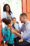 Niños de Saying Goodbye To del padre como se van para la escuela Foto de archivo libre de regalías