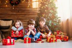 Niños del grupo con los regalos de Navidad soñadores Foto de archivo