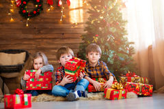 Niños del grupo con los regalos de Navidad soñadores Foto de archivo libre de regalías