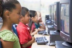 Niños del jardín de la infancia que aprenden utilizar los ordenadores Imagen de archivo