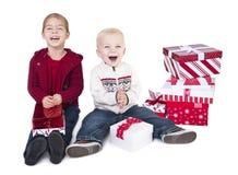 Niños emocionados que abren sus regalos de la Navidad Fotografía de archivo