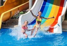 Niños en diapositiva de agua en el aquapark Fotos de archivo