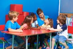 Niños en el circletime listining a hablar de la muchacha Imágenes de archivo libres de regalías
