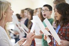 Niños en el grupo cantante que es animado por el profesor Imágenes de archivo libres de regalías