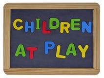 Niños en el juego en letras coloreadas en pizarra Fotos de archivo