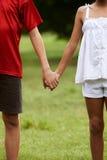 Niños en el muchacho y la muchacha del amor que llevan a cabo las manos Foto de archivo libre de regalías