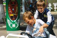 Niños en el área de juego que monta un coche del juguete Nikolaev, Ucrania Foto de archivo libre de regalías