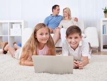Niños en la alfombra usando la tablilla y la computadora portátil Fotografía de archivo